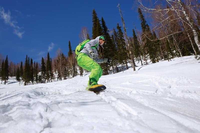 El Snowboarder que hace un lado del dedo del pie talla con el cielo azul profundo en backgro imagen de archivo