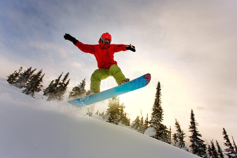El Snowboarder que hace un lado del dedo del pie talla con el cielo azul profundo en backgro fotos de archivo libres de regalías