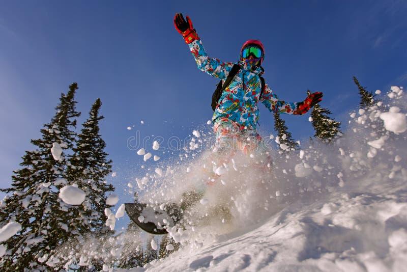 El Snowboarder que hace un lado del dedo del pie talla con el cielo azul profundo en backgro imágenes de archivo libres de regalías
