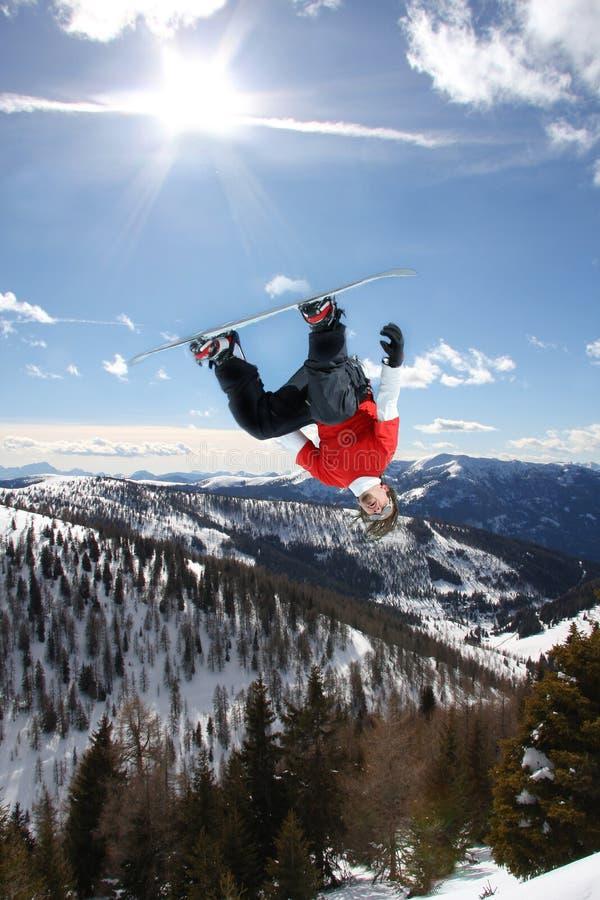 El Snowboarder que salta contra el cielo imagen de archivo