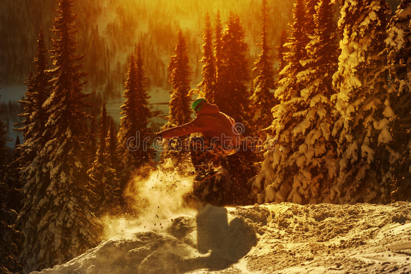 El Snowboarder que salta contra el cielo de la puesta del sol fotos de archivo libres de regalías