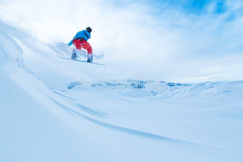 El Snowboarder que salta de la roca fotos de archivo libres de regalías
