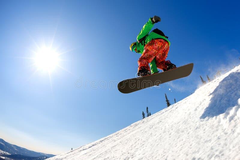 El Snowboarder que salta del trampolín contra el cielo fotografía de archivo