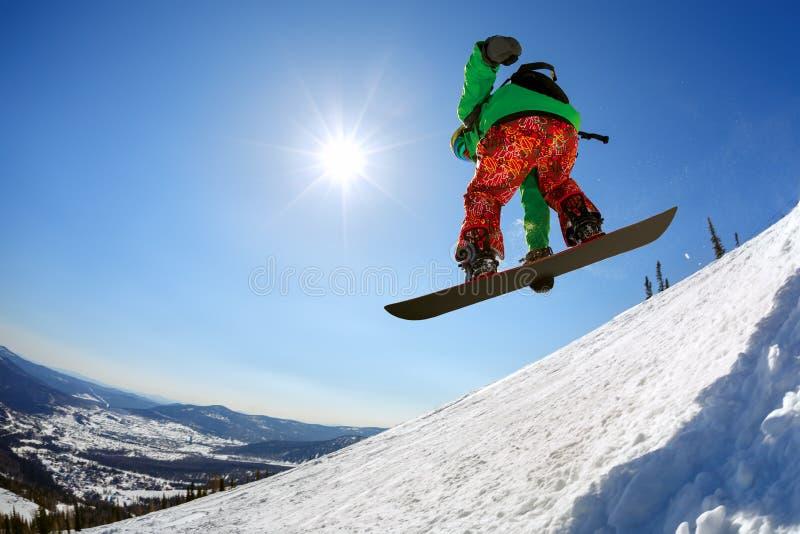 El Snowboarder que salta del trampolín contra el cielo imagenes de archivo