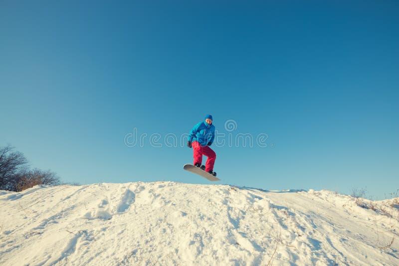 El Snowboarder que salta en fondo del cielo azul imagen de archivo