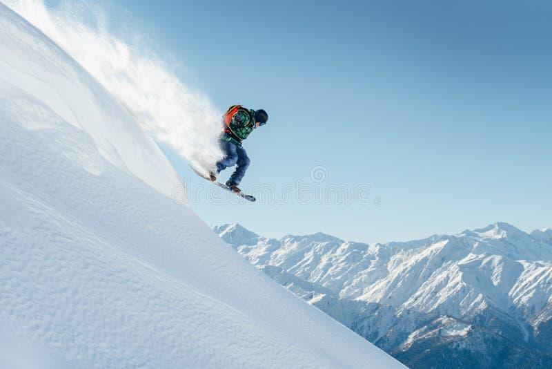 El Snowboarder que salta en la ladera escarpada imagen de archivo libre de regalías