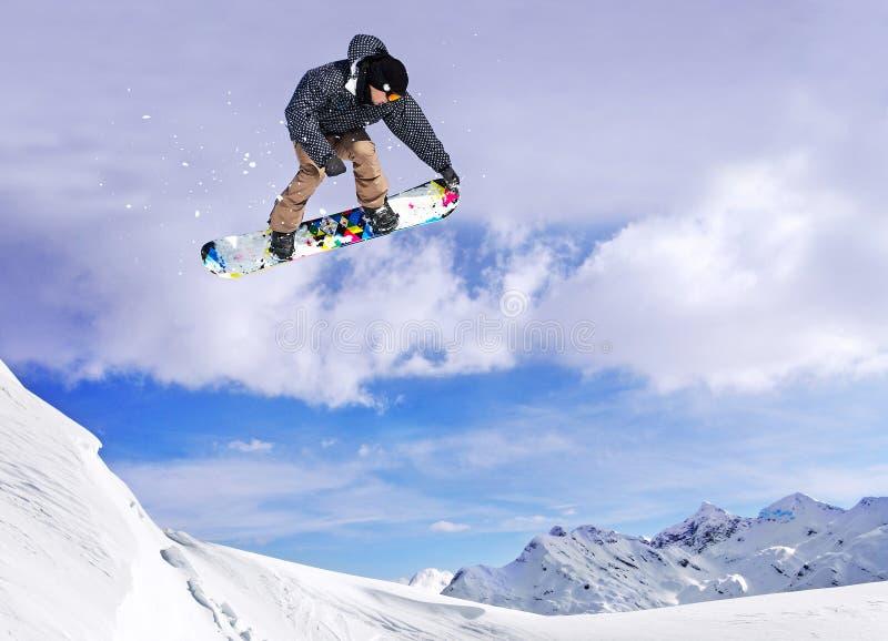 El Snowboarder que salta a través del aire con el cielo en fondo foto de archivo