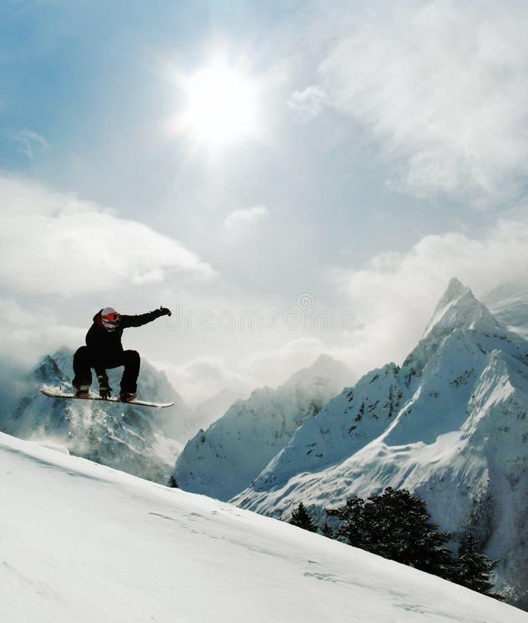 El Snowboarder que salta y que monta entre las montañas foto de archivo