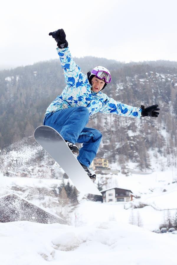 El Snowboarder salta en snowboard foto de archivo