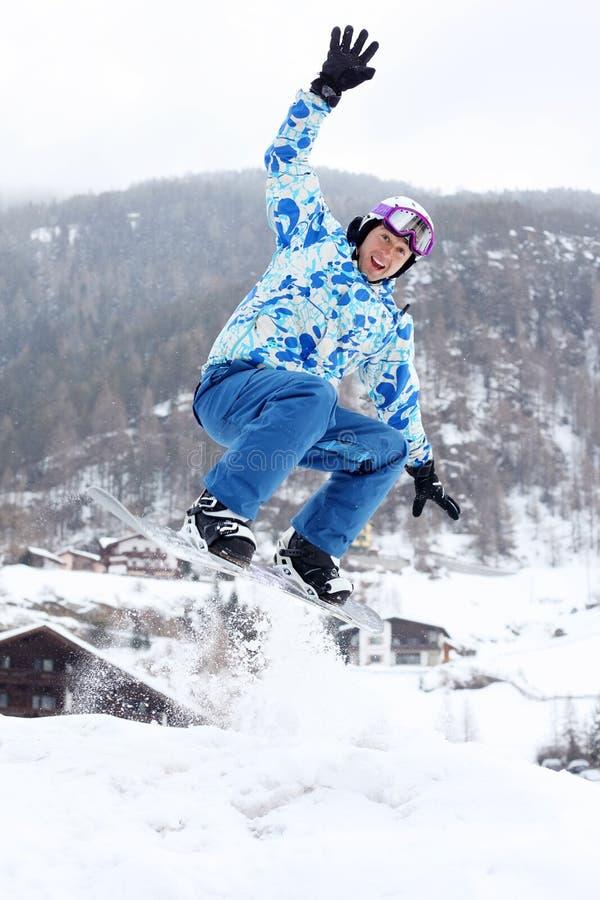 El Snowboarder salta en snowboard y agita a mano foto de archivo