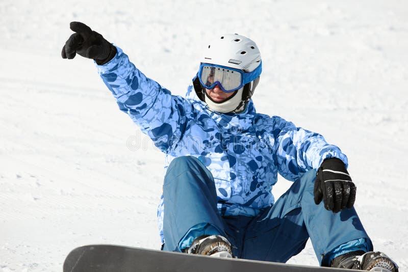 El Snowboarder se sienta en la ladera nevosa imagenes de archivo