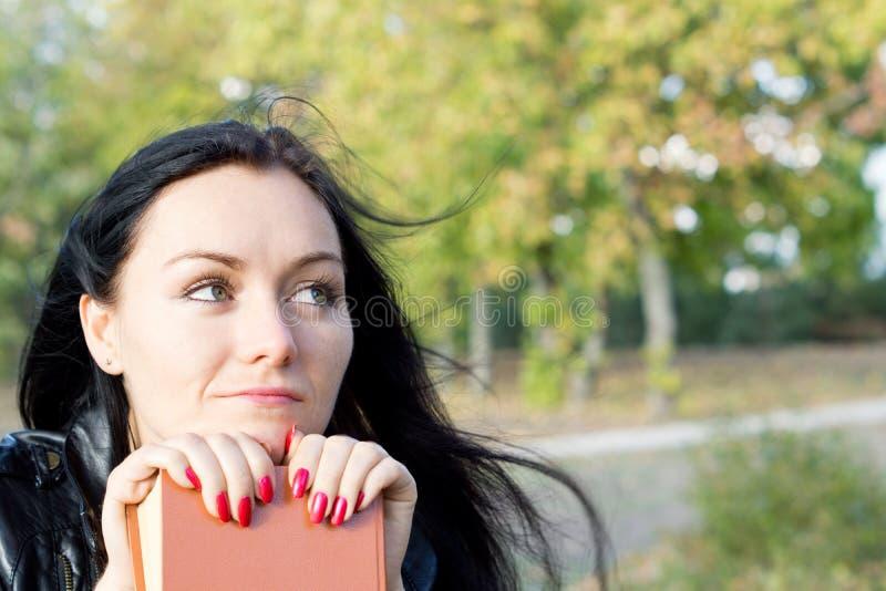 El soñar despierto que se sienta de la mujer con su libro foto de archivo