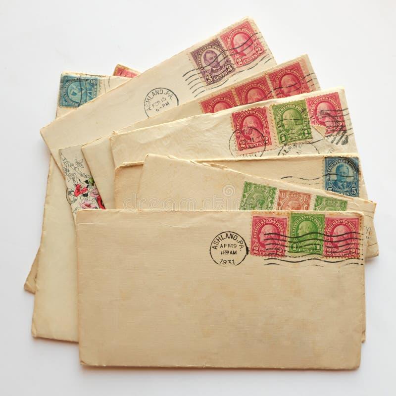 El sobre en blanco en la pila de viejas letras, posts de los sobres sella imágenes de archivo libres de regalías