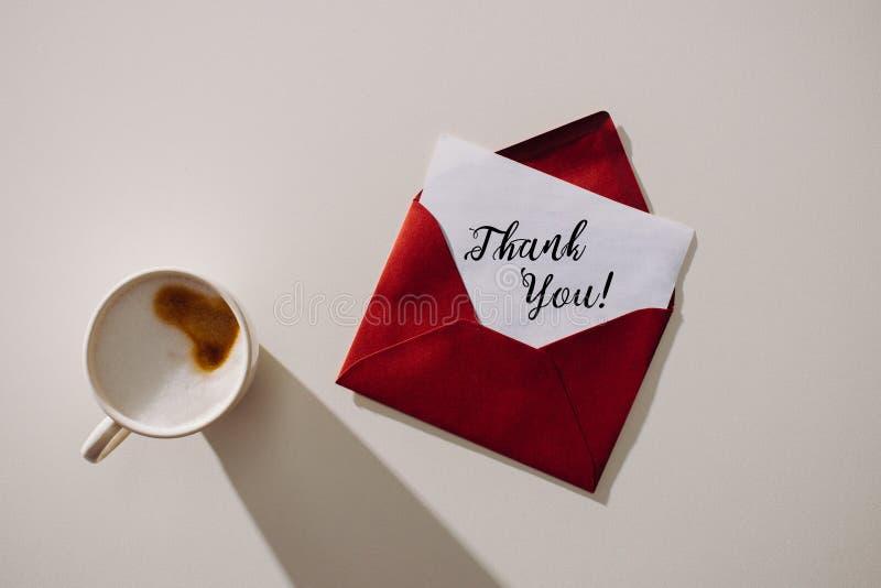 el sobre rojo con le agradece las letras en el papel y la taza de café de papel imagenes de archivo