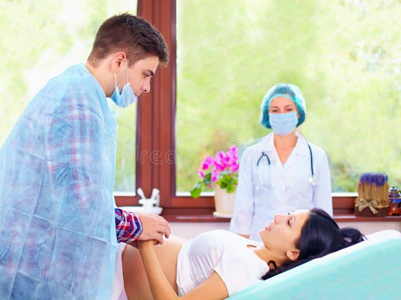El socio ayuda a su esposa durante el parto fotos de archivo