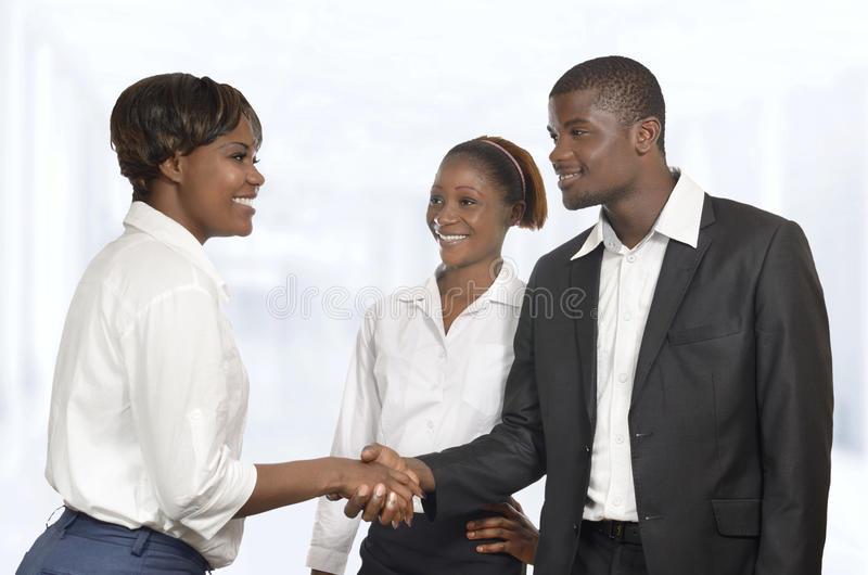 El socio comercial de tres africanos sacude las manos en la reunión fotografía de archivo libre de regalías