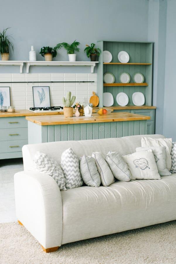 El sofá brillante y muchas almohadas en él está en la sala de estar o la cocina fotografía de archivo libre de regalías