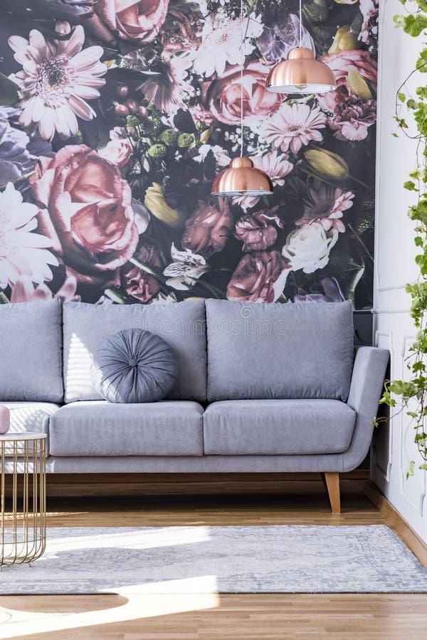 El sofá gris contra las flores wallpaper en inte femenino de la sala de estar imagen de archivo libre de regalías