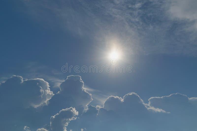 El sol brilla brillantemente en el cielo azul claro Las nubes de tormenta grandes están viniendo imágenes de archivo libres de regalías