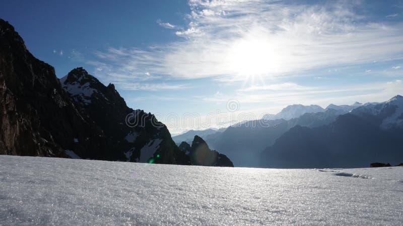 El sol brilla brillantemente Vista de montañas nevosas, del cielo azul, del acantilado y de las nubes blancas imagen de archivo libre de regalías