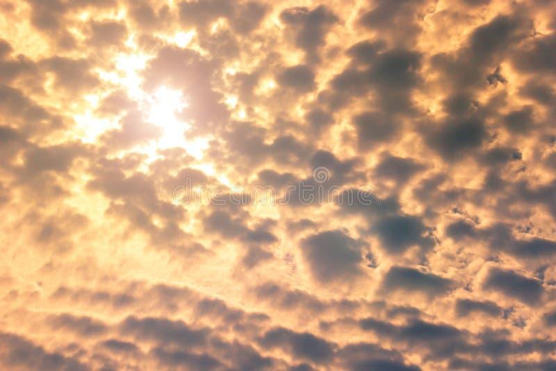 El sol brilla a través de las nubes en el fondo del cielo azul fotos de archivo