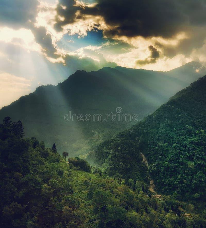 El sol de la mañana irradia venir a través de las nubes y caer en la vegetación verde en la montaña foto de archivo