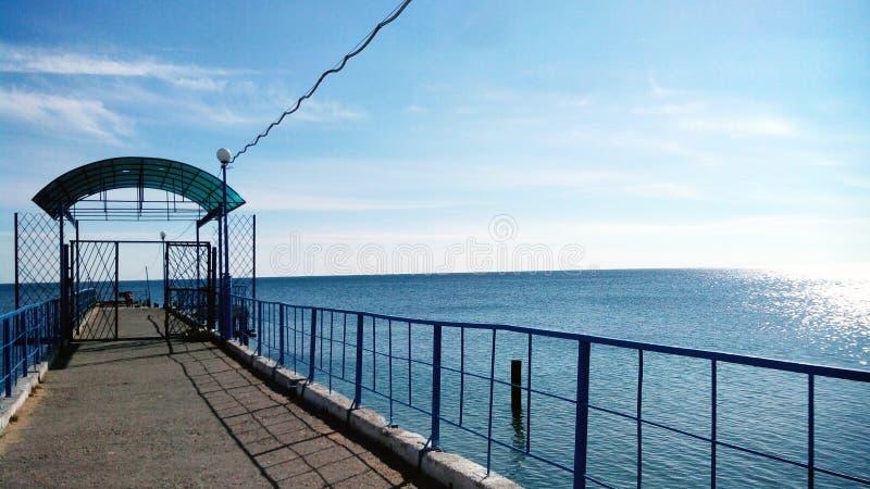 El sol del mar del embarcadero se nubla el cielo azul fotos de archivo