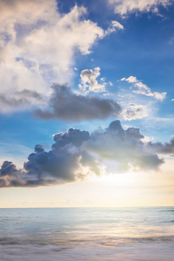 El sol en nubes. el sol brilla a través de las nubes grises oscuras, la luz se refleja en el mar azul y tranquilo, un hermoso pai imágenes de archivo libres de regalías