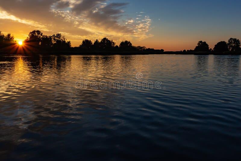 El sol hermoso irradia durante puesta del sol en los plas de Zoetermeerse del lago fotografía de archivo libre de regalías