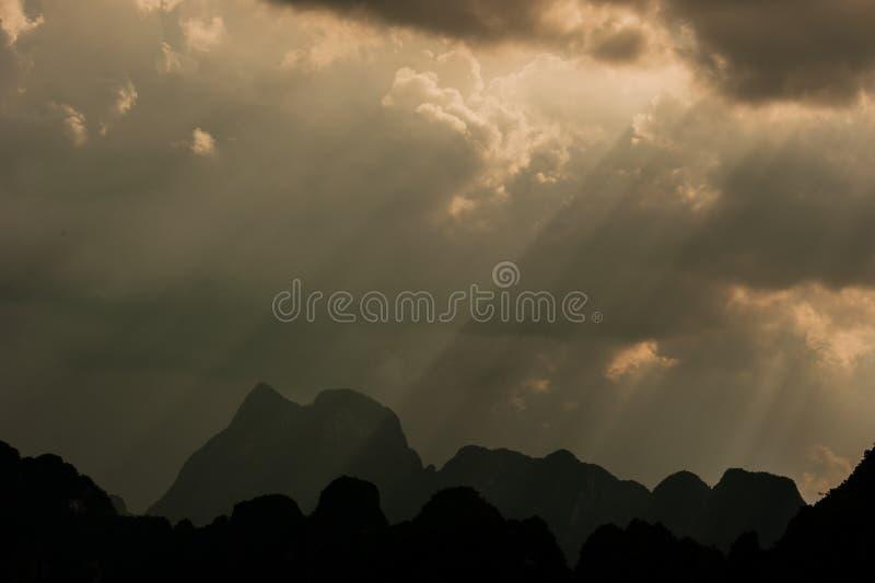 El sol hermoso irradia a través de las nubes sobre las montañas, igualando el lig foto de archivo