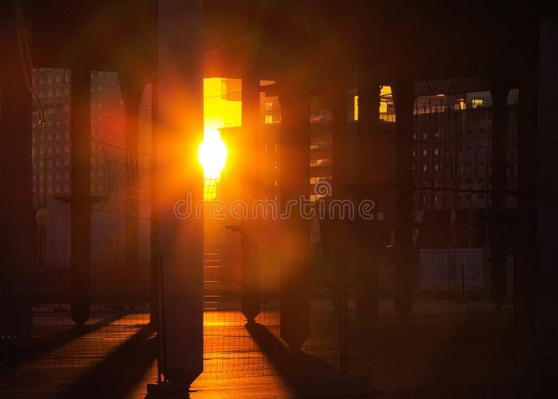 El sol rojo caliente brilla a través de polos concretos Puesta del sol de la tarde en el co fotografía de archivo libre de regalías
