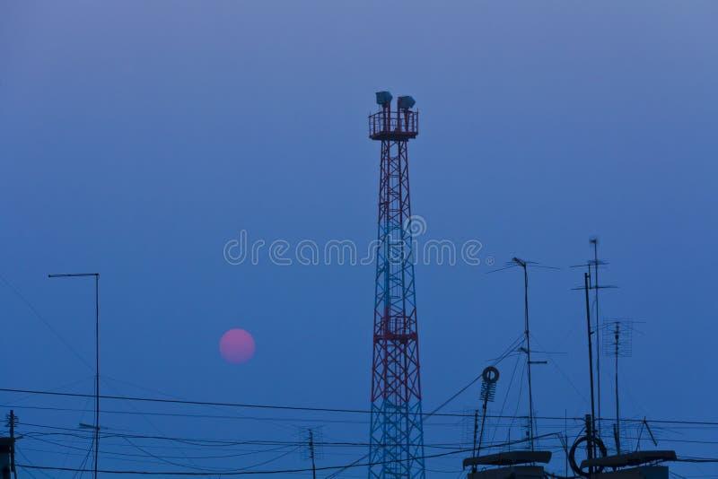 El sol rojo fija sobre el tejado de una casa de ciudad, alambres, antenas, torre fotografía de archivo libre de regalías