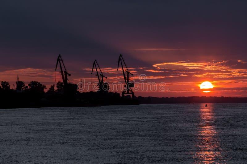 El sol sangriento desciende en el agua a través de las nubes imagen de archivo libre de regalías
