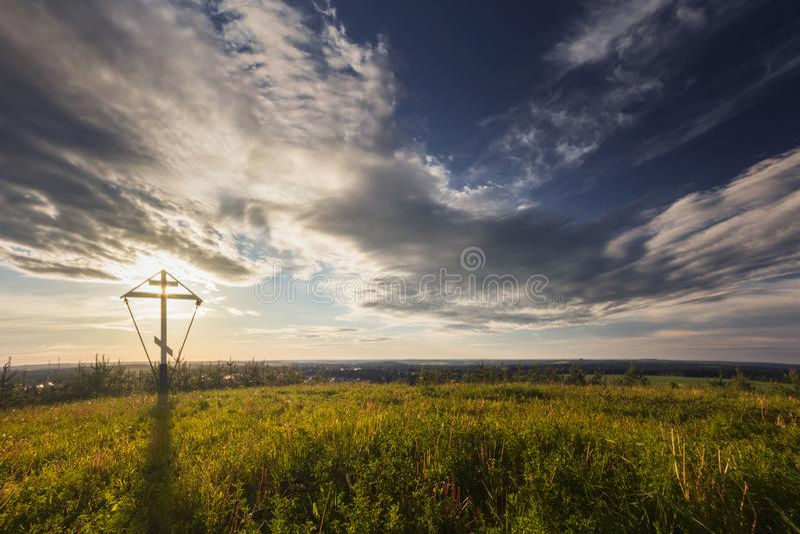 El sol se levanta sobre las nubes del mar y del oro amanecer La cruz ortodoxa grande es iluminada por la luz del sol fotos de archivo