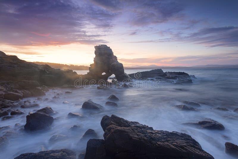 El sol se pone detrás de la roca en arco de la cueva foto de archivo