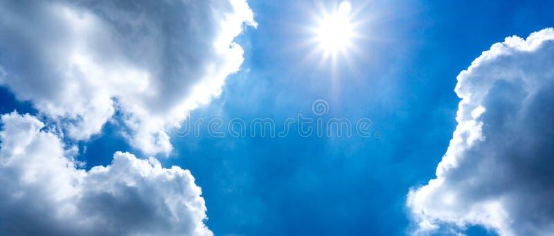 El sol shinning en el cielo azul y la nube de cúmulo imagen de archivo