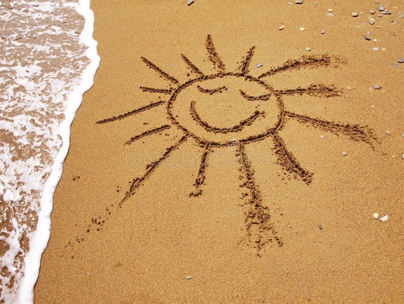 El sol sonriente drenado en la arena imagen de archivo