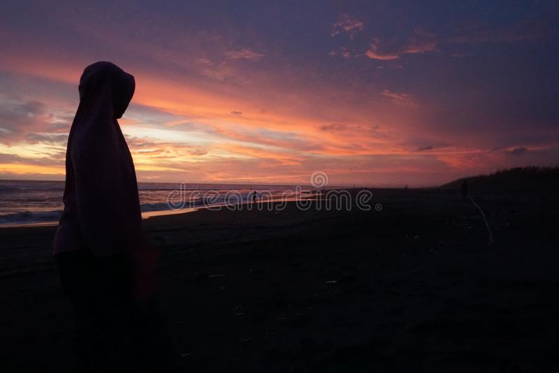 El sol sube durante el verano en la playa con el primero plano del silhoutte humano fotografía de archivo libre de regalías