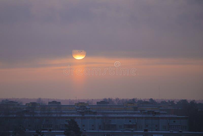 El sol sube en una mañana brumosa escarchada sobre la ciudad fotografía de archivo