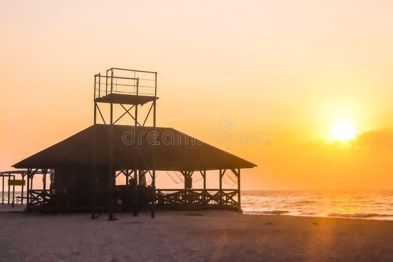 El sol sube sobre la casa por el mar imagenes de archivo