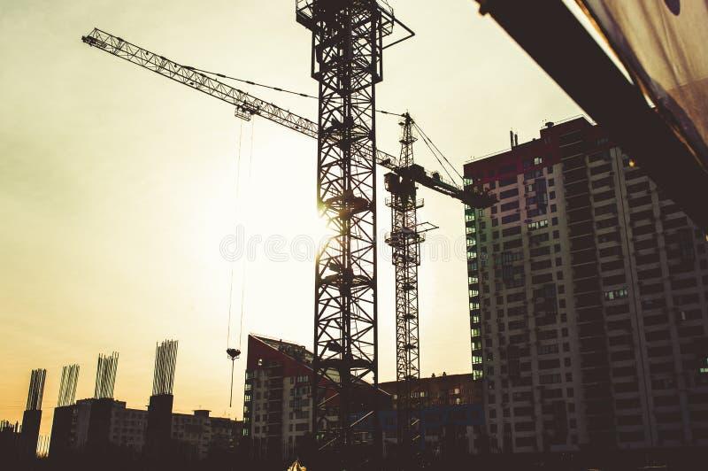 El solar con el bloque de gran altura bajo construcci?n en un ambiente urbano domin? por una gr?a industrial grande fotografía de archivo