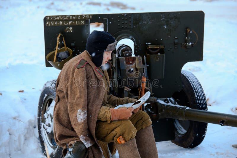 El soldado de ejército rojo está leyendo el periódico que se sienta en el arma divisional M1942 ZiS-3 de 76 milímetros imagenes de archivo