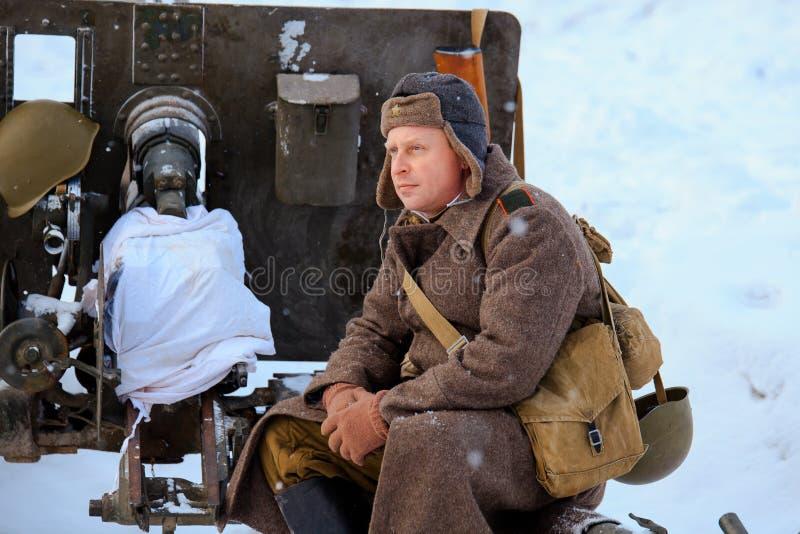 El soldado de ejército rojo se está sentando en el arma divisional M1942 ZiS-3 de 76 milímetros foto de archivo