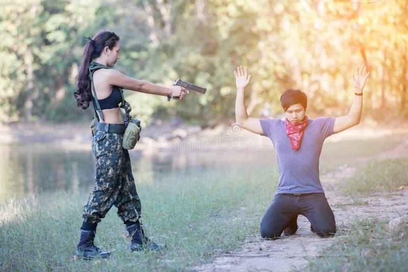 El soldado de la mujer con una pistola arrestó al culpable fotos de archivo