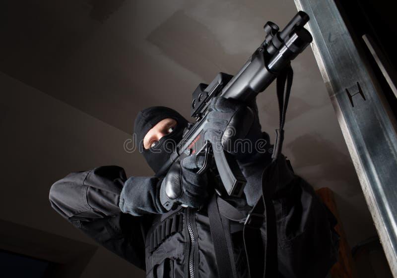 El soldado de las fuerzas especiales es que apunta y que tira en la blanco imagen de archivo