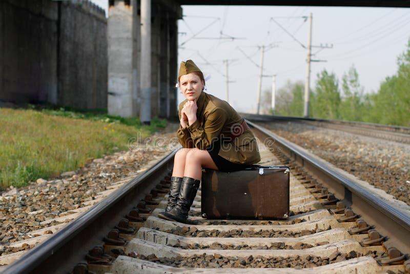 El soldado de sexo femenino soviético en el uniforme de la Segunda Guerra Mundial se sienta en una maleta en las vías del tren imagen de archivo