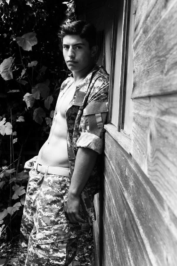 El soldado de sexo masculino apuesto en choza de madera siguiente permanente del uniforme muestra apagado el ABS y Pecs musculare imagenes de archivo