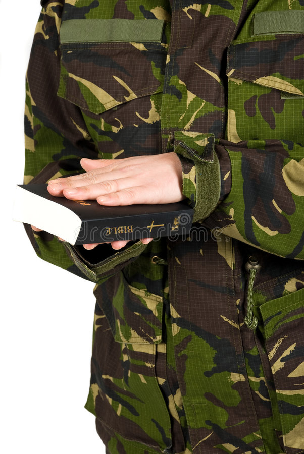 El soldado jura con la mano en la biblia imagen de archivo