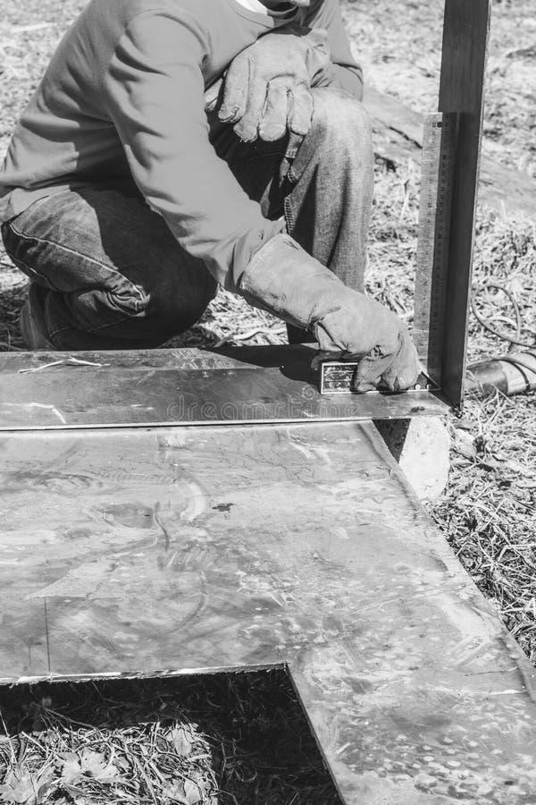 El soldador de sexo masculino hace medidas del corchete menor/mayor de acero de la regla de las piezas de metal fotos de archivo libres de regalías