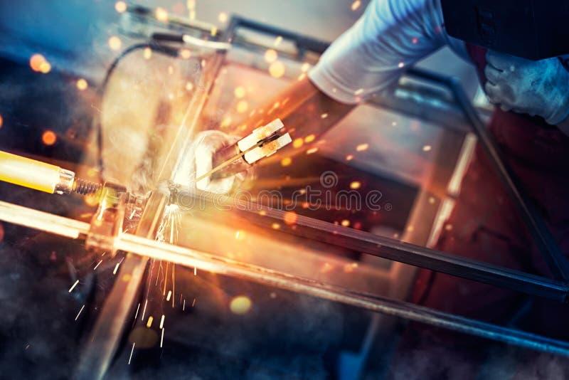 el soldador del hombre con guantes de la construcción y una máscara de soldadura está funcionando y se suelda con autógena entusi foto de archivo